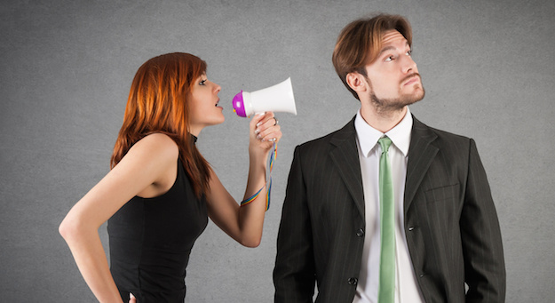 Woman shouting to man with megaphone against grunge background.